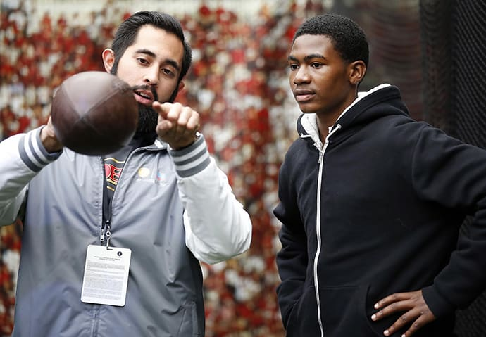 Josiah Rodriguez, left, educator at the 49ers Museum, explains the science behind a pass in the Chevron STEM Zone in Super Bowl City on Tuesday, Feb. 2, 2016 in San Francisco. The Chevron STEM Zone is an interactive exhibit that brings the science behind football to life for fans in Super Bowl City. (Tony Avelar/AP Images for Chevron)