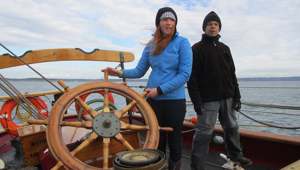 Student at the helm of a boat Place-Based Ed Feature Image