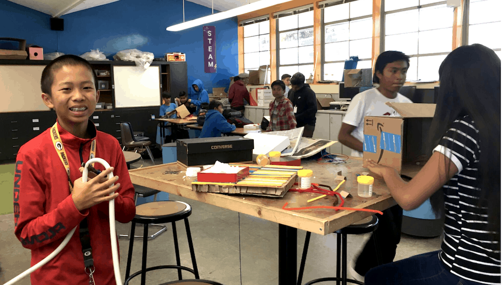A student standing in a makerspace classroom at VIDA, holding some sort of tube contraption and smiling