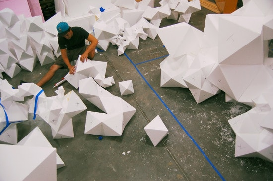 Student building large paper geometric shapes on cement floor