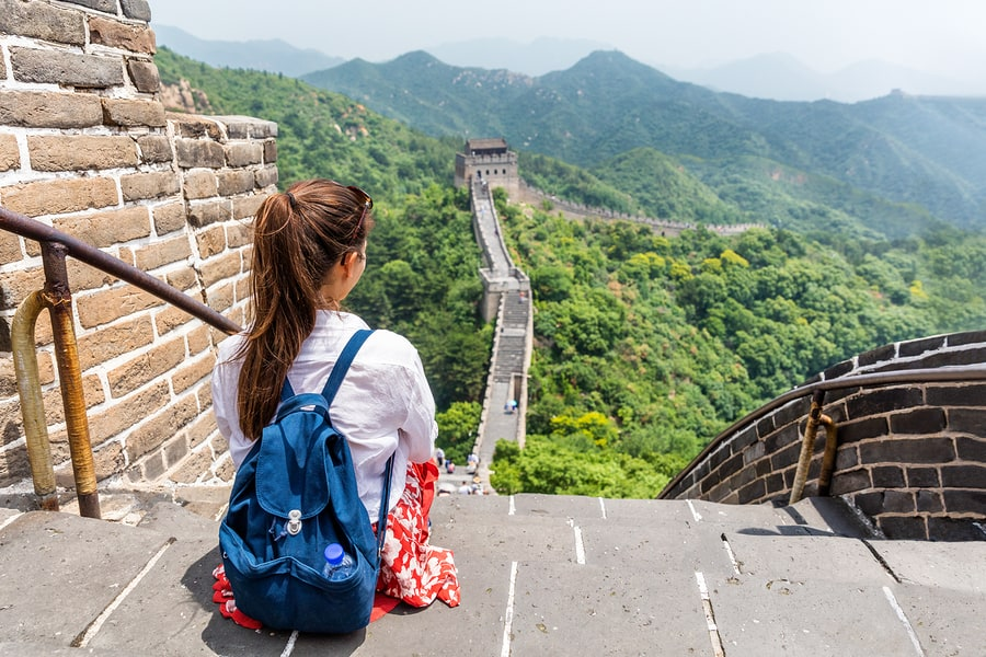 student with backpack sitting on great wall of china gazing at the horizon and experiencing deeper learning