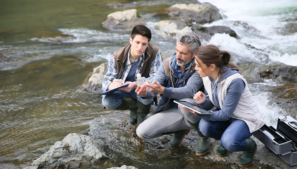 Two Students and their teacher sitting on the klamath river and engaging in a place-based learning science project