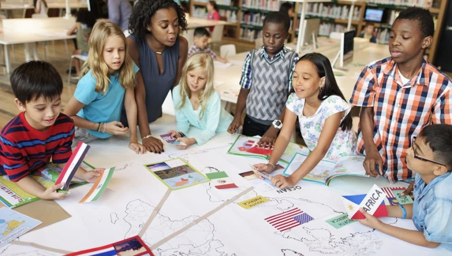 diverse students working on a project placing country flags on a map in a classroom guided by inclusiveness and equity for all