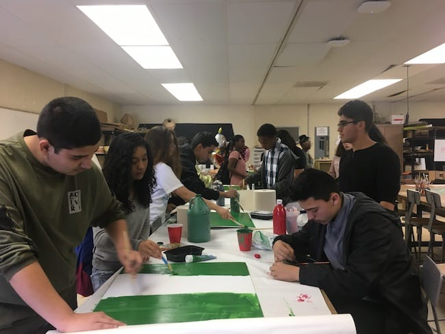 Students standing around a table painting and working on projects