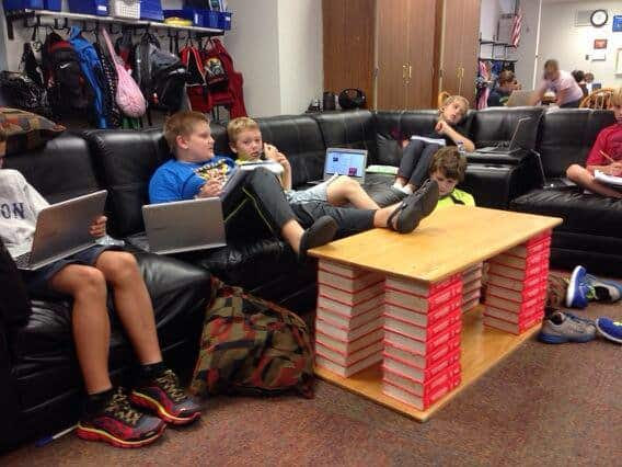 Students sit around a creatively built table with laptops.